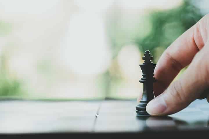 Homme tenant un pion aux échecs pour montrer l'attractivité de son entreprise